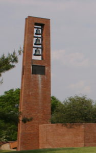 Shows the brick bell tower with 3 bells