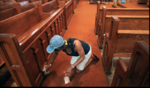 Photo of a man cleaning a church pew